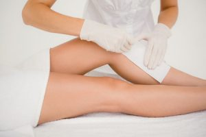 42398084 - mid section of therapist waxing womans leg at spa center